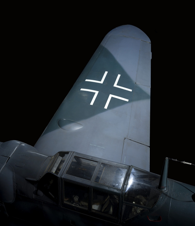 Top of wing of gray Messerschmitt Bf 109 aircraft with white cross