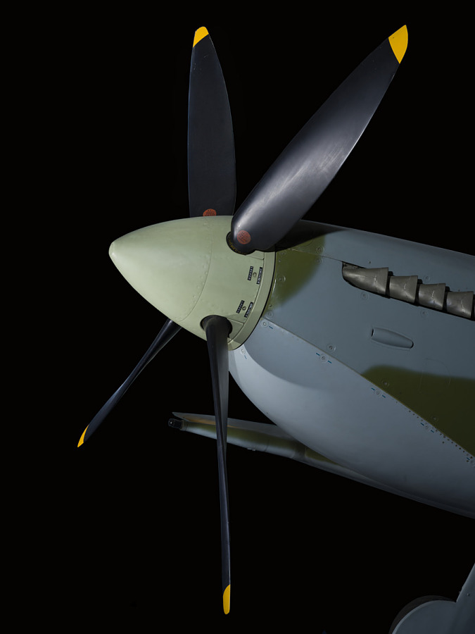 Nose and black four-blade propellers with yellow tips on green and blue Spitfire aircraft in                 museum