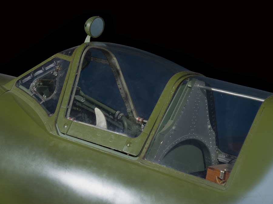 Outside of cockpit of green and blue Spitfire aircraft