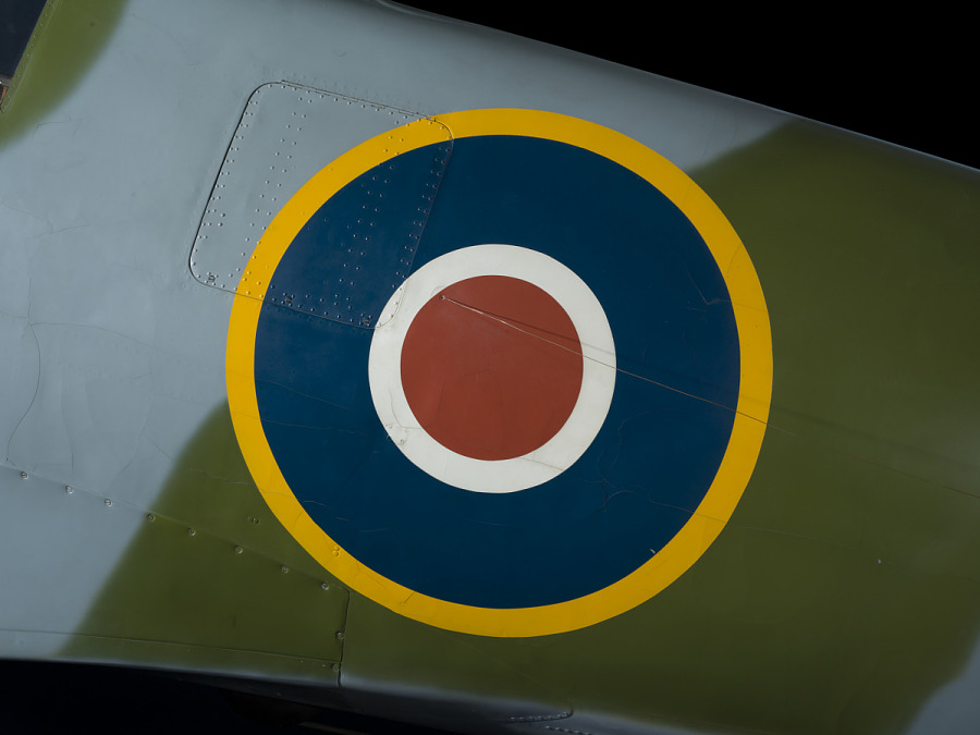 British roundel with yellow border on fuselage of green and blue Spitfire aircraft