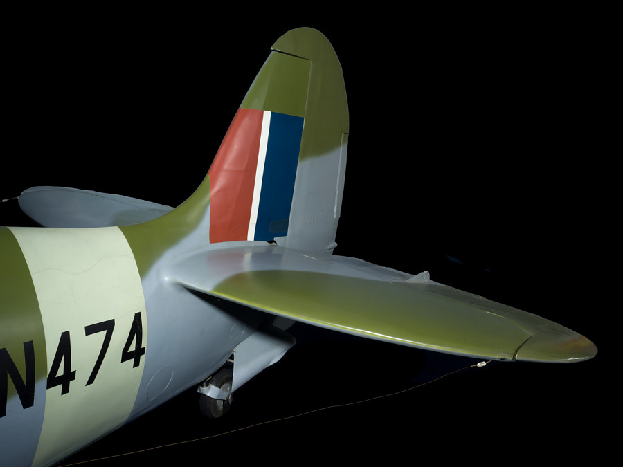 Tail of green and blue Spitfire aircraft with red, white, and blue fin flash design