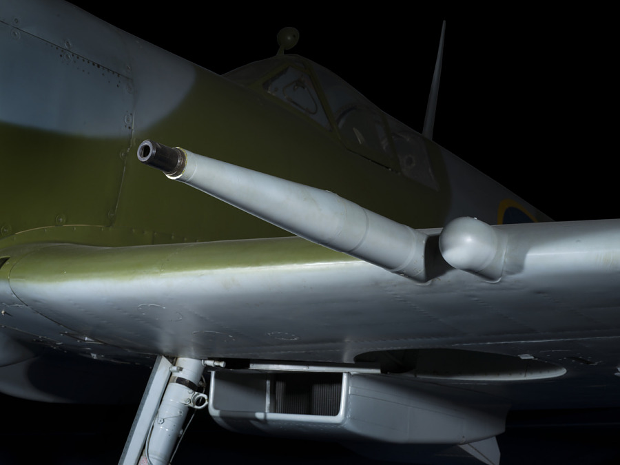 Long Hispano Cannon on wing of green and blue Spitfire aircraft