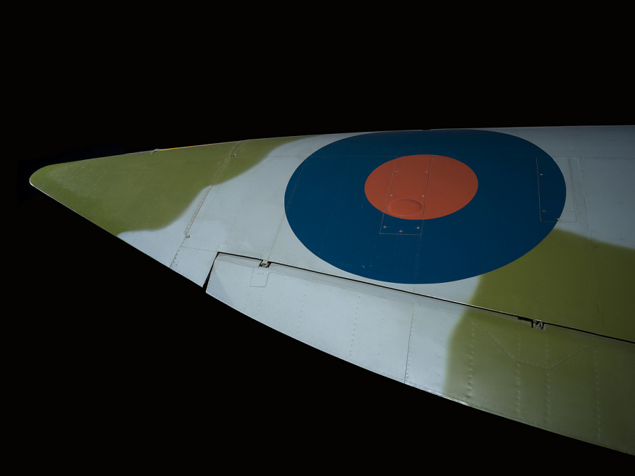 Blue and red British roundel on wing of green and blue Spitfire aircraft