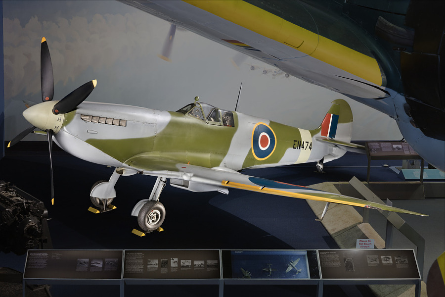 View of green and blue Spitfire aircraft in museum display
