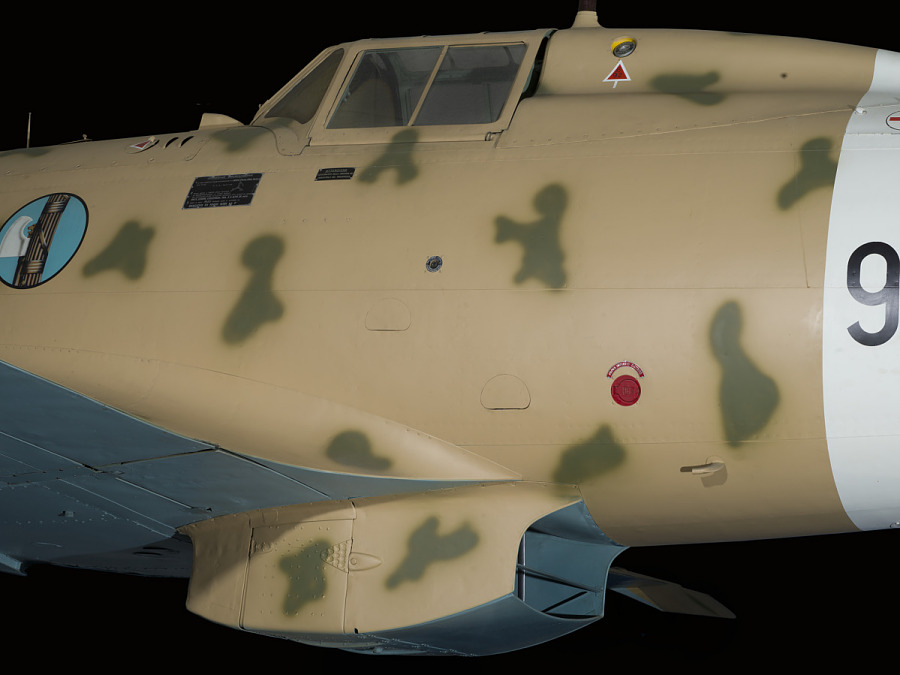 Outside of cockpit of tan Macchi C.202 Folgore aircraft with blue roundel on fuselage