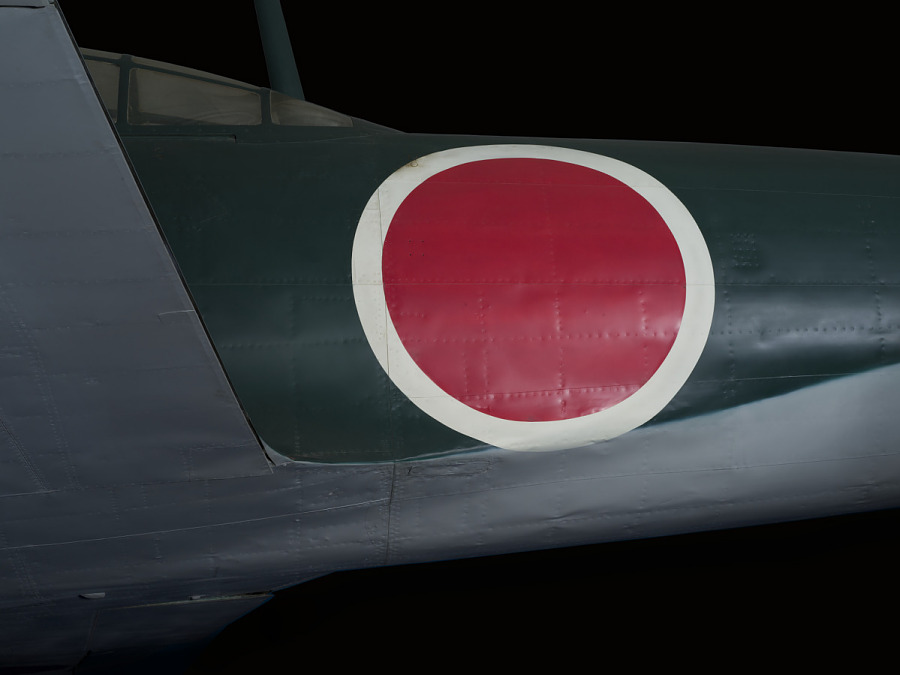 Closeup view of insignia painted on the side of Zero Fighter aircraft, a red disc surrounded by a white circle