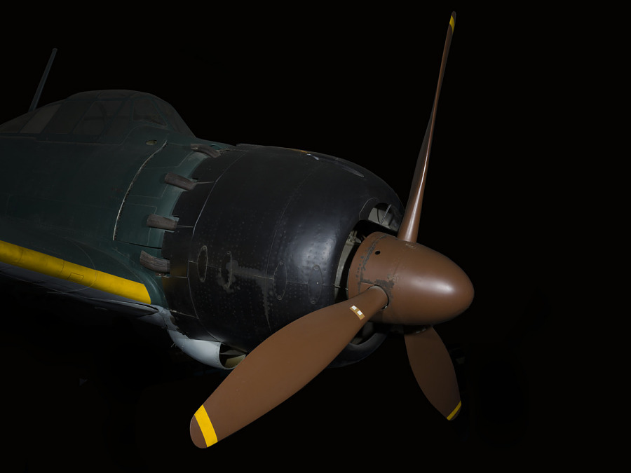 Brown tri-blade propeller on black nose of green Zero Fighter aircraft