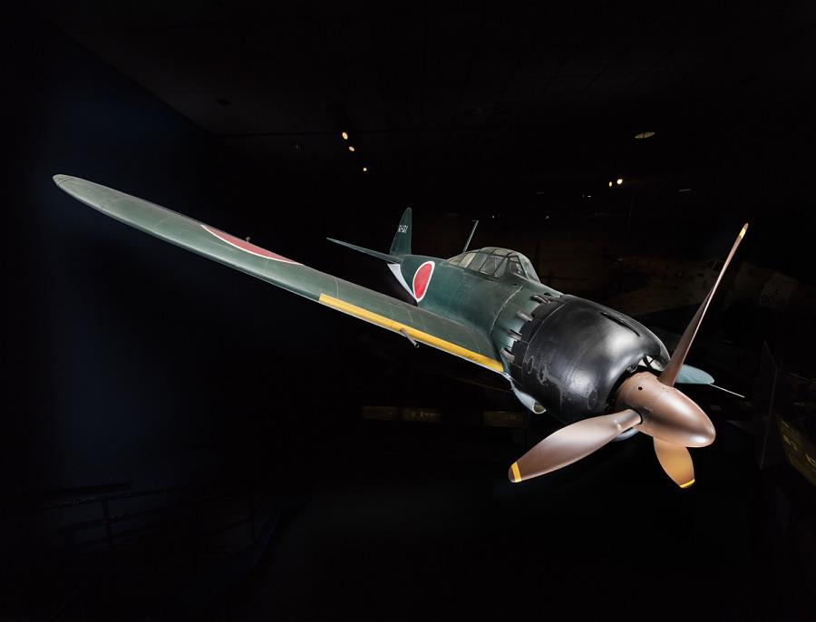 Green tri-blade propellered Zero Fighter aircraft against a dark background