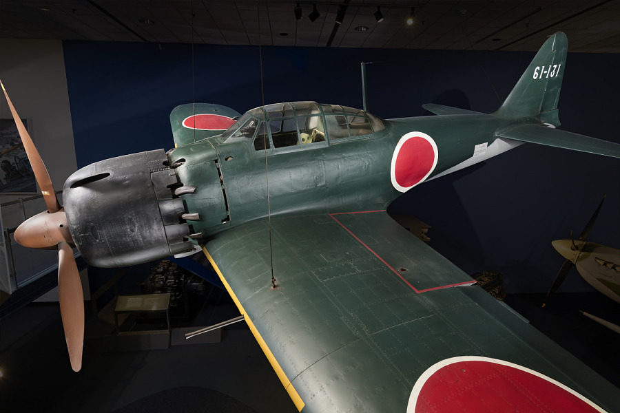 Side of green tri-blade propellered Zero Fighter aircraft hanging in museum