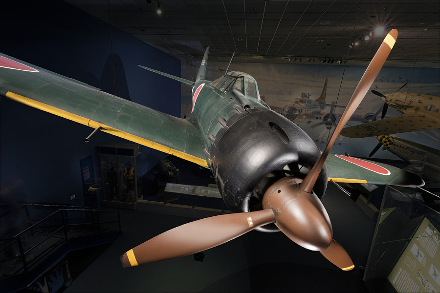 Closeup view of propellered Zero Fighter aircraft hanging in museum