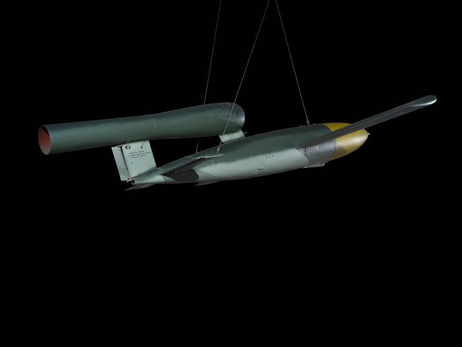 Side of sleek, silver cruise missile with wings, and yellow nose