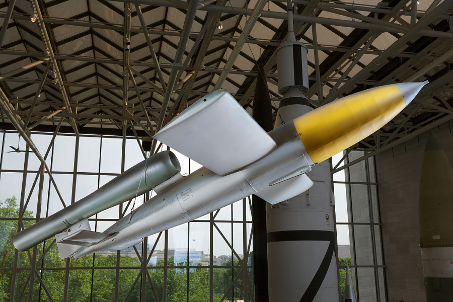 Sleek, silver cruise missile with wings, and yellow nose hanging in museum