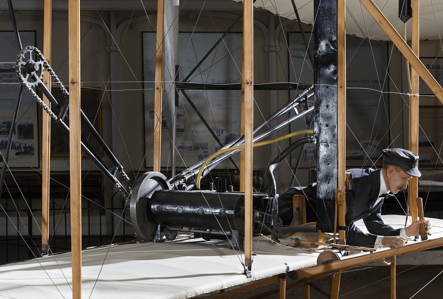 Model of Wright Brother laying flat in 1903 Wright Flyer in museum