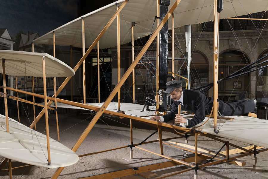 Side of 1903 Wright Flyer with model of Wright Brother laying flat in aricraft