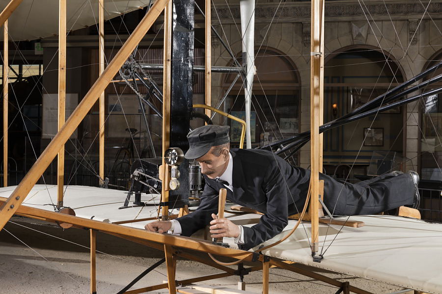 Model of one of the Wright Brothers laying flat in 1903 Wright Flyer in museum