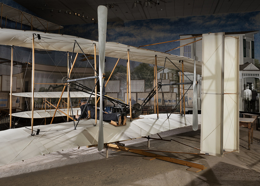 Rear of 1903 Wright Flyer with model of Wright Brother laying flat in aricraft