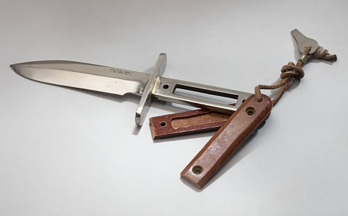 Steel knife with movable, hollow wooden handles and leather tong