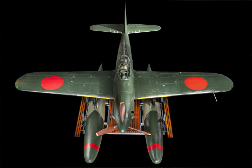 Green bomber with red roundels on the wings and twin floats in place of wheels, seen from above