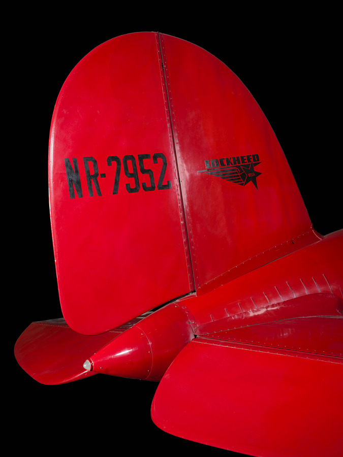 "Tail of red Amelia Earhart Lockheed Vega 5B aircraft with ""NR-7952"" and lockheed logo in black"