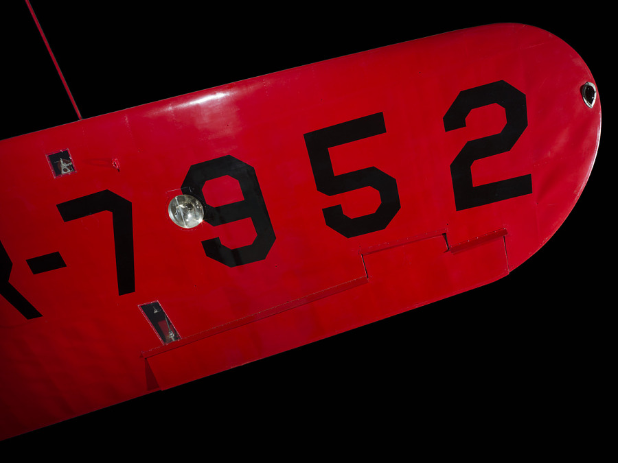 "Under wing of red Amelia Earhart Lockheed Vega 5B aircraft with ""7952"" in black letters"