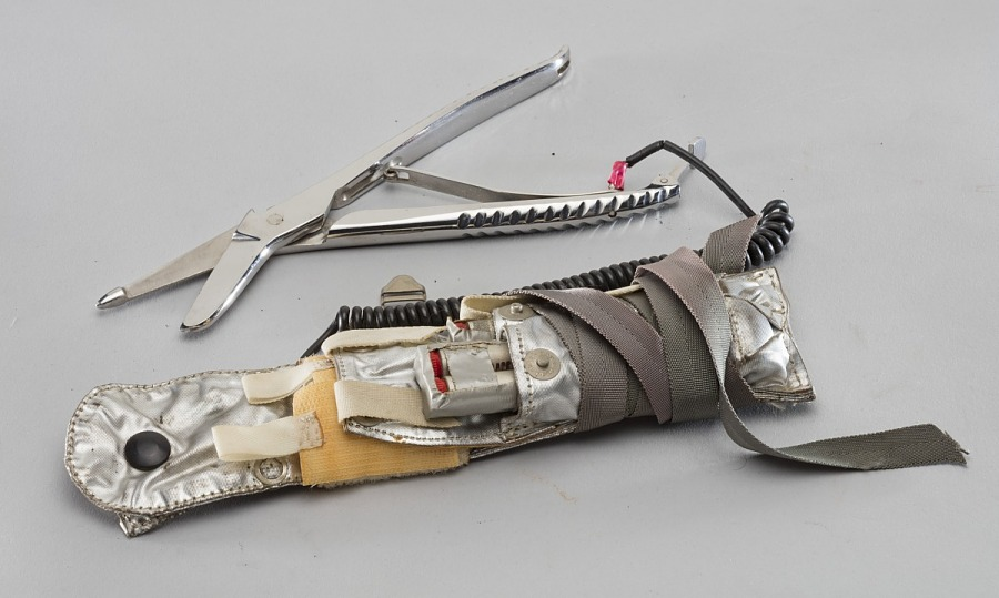 Silver first aid kit with green straps and scissors attached by cord