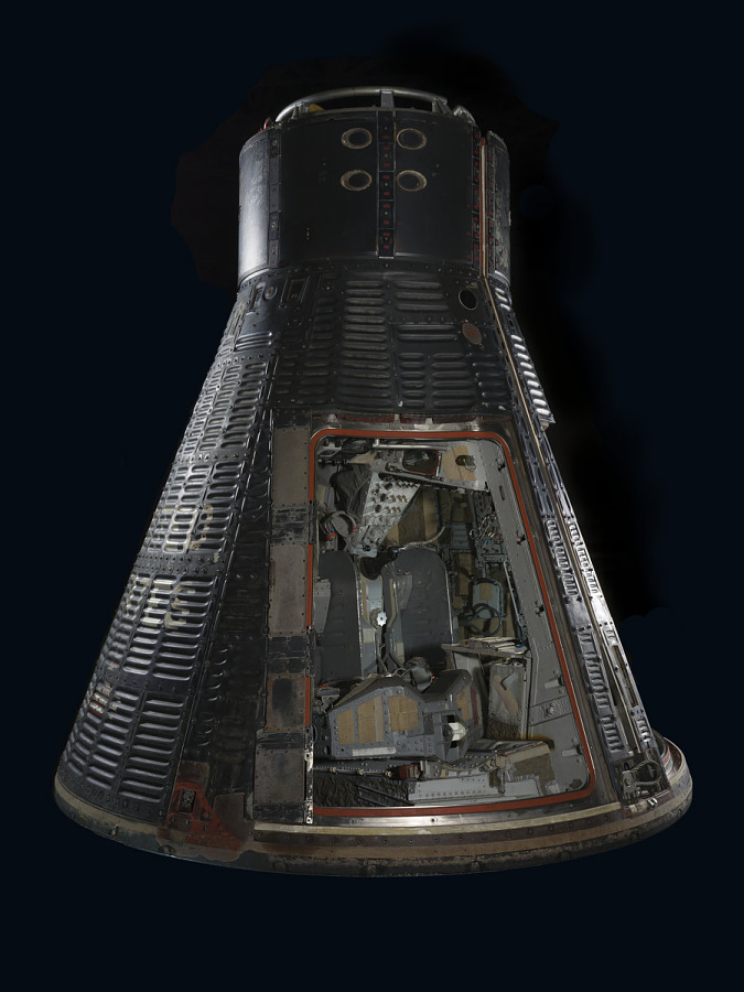 Two-man bell-shaped spacecraft with black shingles, heatshield, and two crew egress hatches.