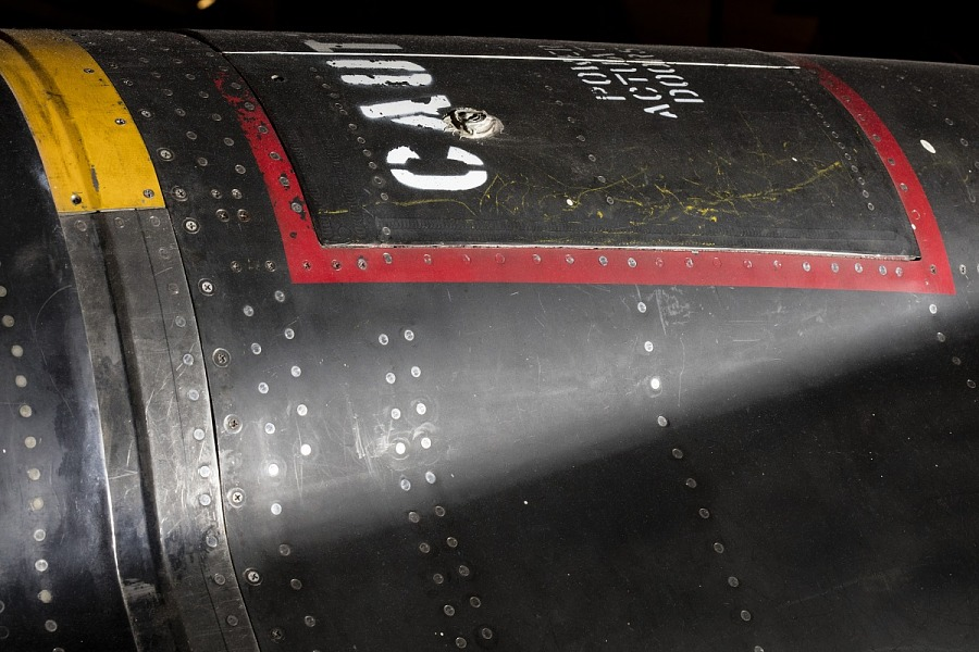 """Red square outline and """"Caution"""" in white lettering on black titanium North American x-15                 aircraft"""