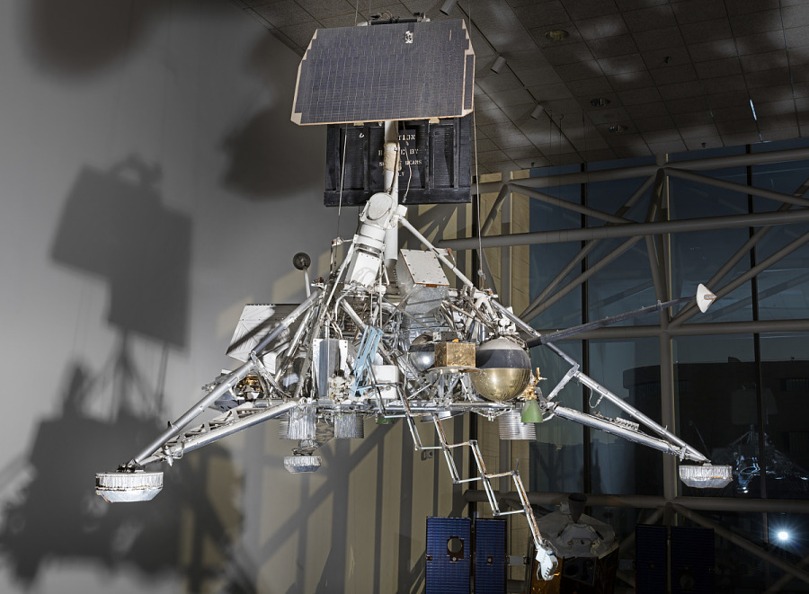Metal lunar lander with three triangular space frame legs connected to central body with panels                 hanging in museum