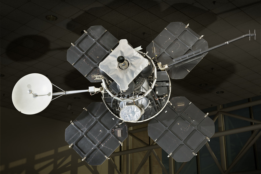 Lunar lander with four square solar panels attached to central instrument box and round                 satellite dish hanging in museum