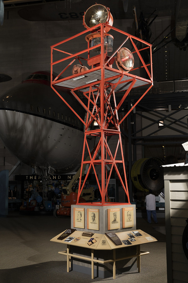 Red metal framed Airway Beacon with beacon light on top and Tower in museum