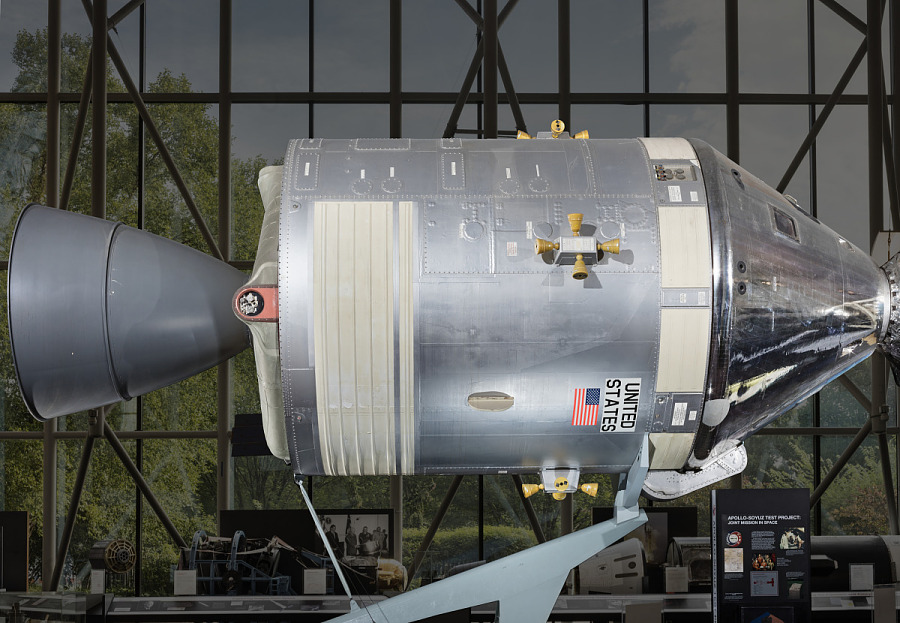Side of metal conical command module with cylindrical module in museum