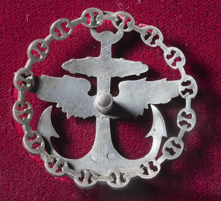 Back view of pin shaped as a silver anchor with wings surrounded by a wreath of chain links