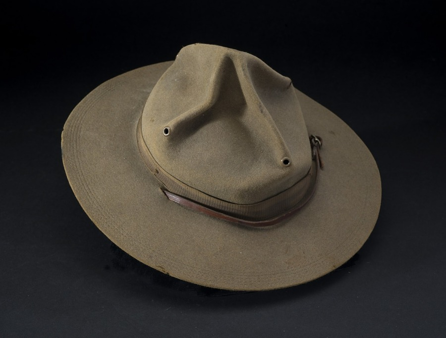 Olive drab felt campaign hat with eyelets on top and leather belt around crown
