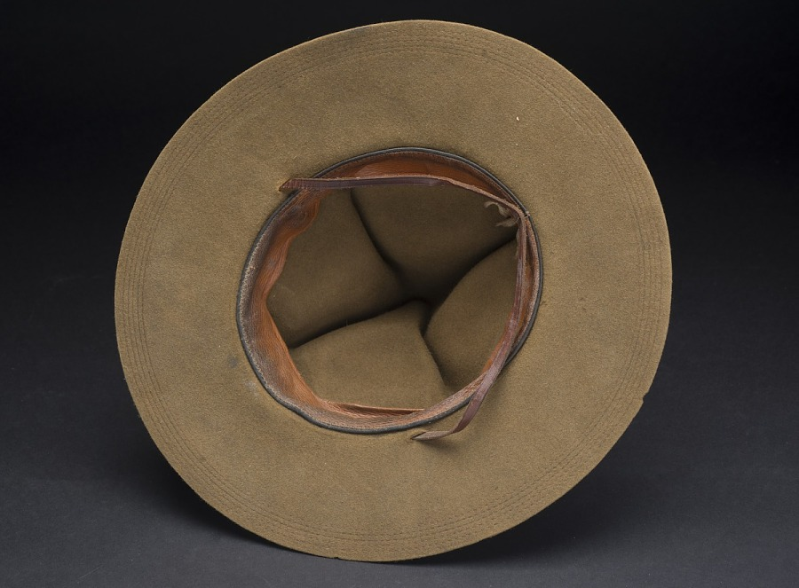 Interior of olive drab felt campaign hat, showing worn sweatband and leather chin strap