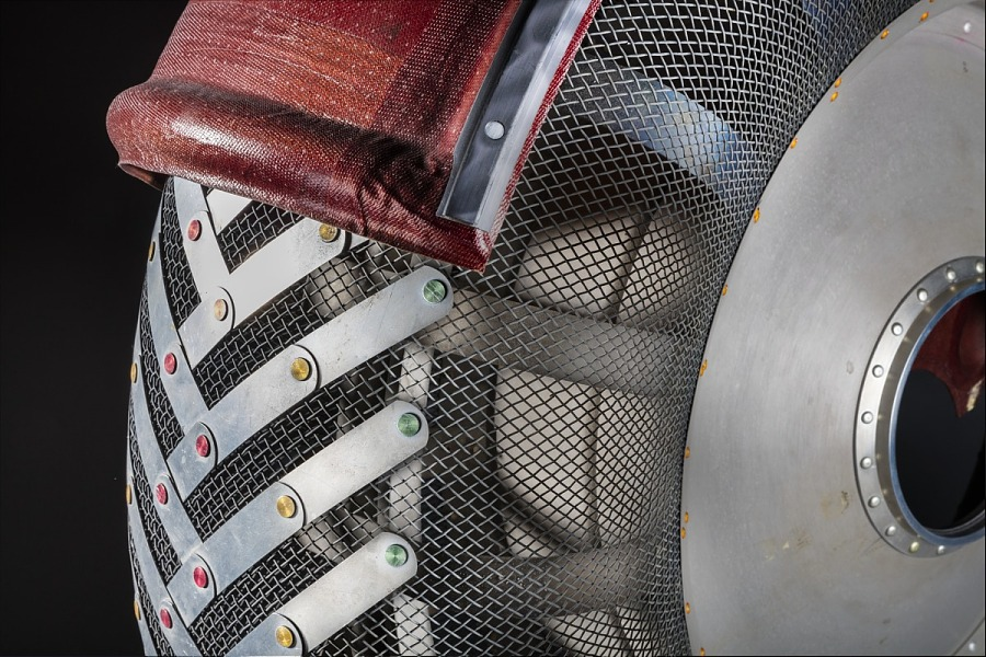 Close up of steel wire and aluminum Lunar Rover wheel with rust colored fender