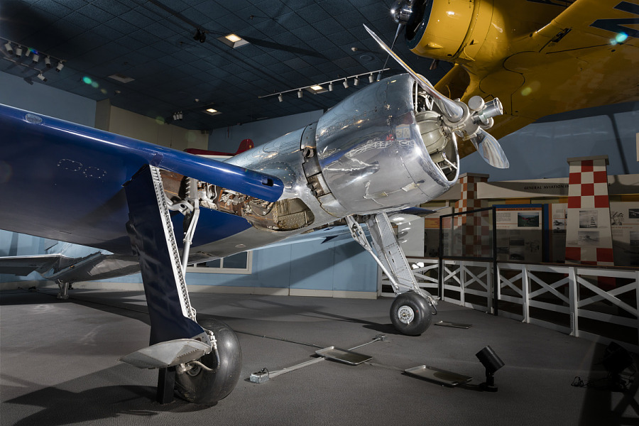 Front of metalic silver and blue Hughes H-1 Racer aircraft with propeller and engine in museum