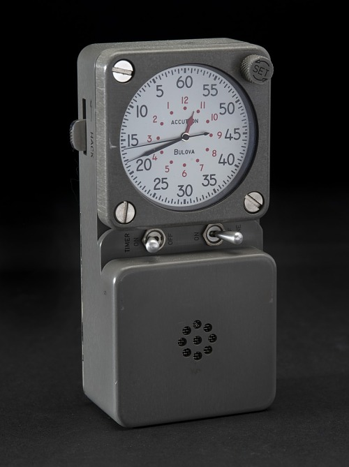 Black rectangular portable timer with clock, two toggle switches, set dial, and hack switch