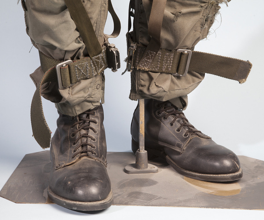 Black leather flying boots with olive-green pants on mannequin