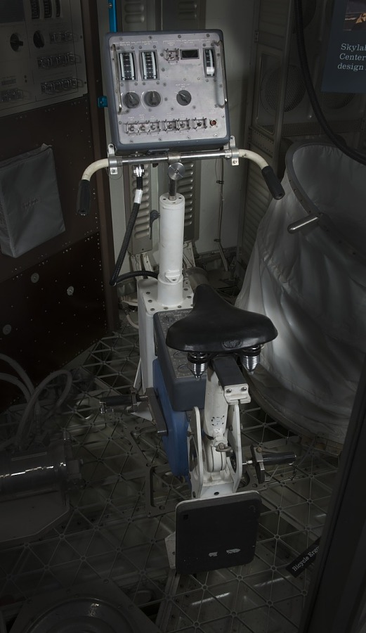 Stationary bicycle with white frame and control panel at handlebar