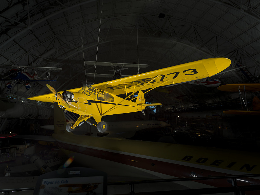 Left front view of yellow monoplane hanging in museum