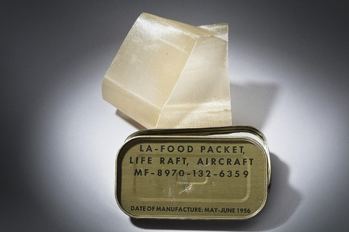 """Metal survival ration container with rounded corners and lid with black lettering, """"LA-FOOD                 PACKET, LIFE RAFT, AIRCRAFT..."""""""