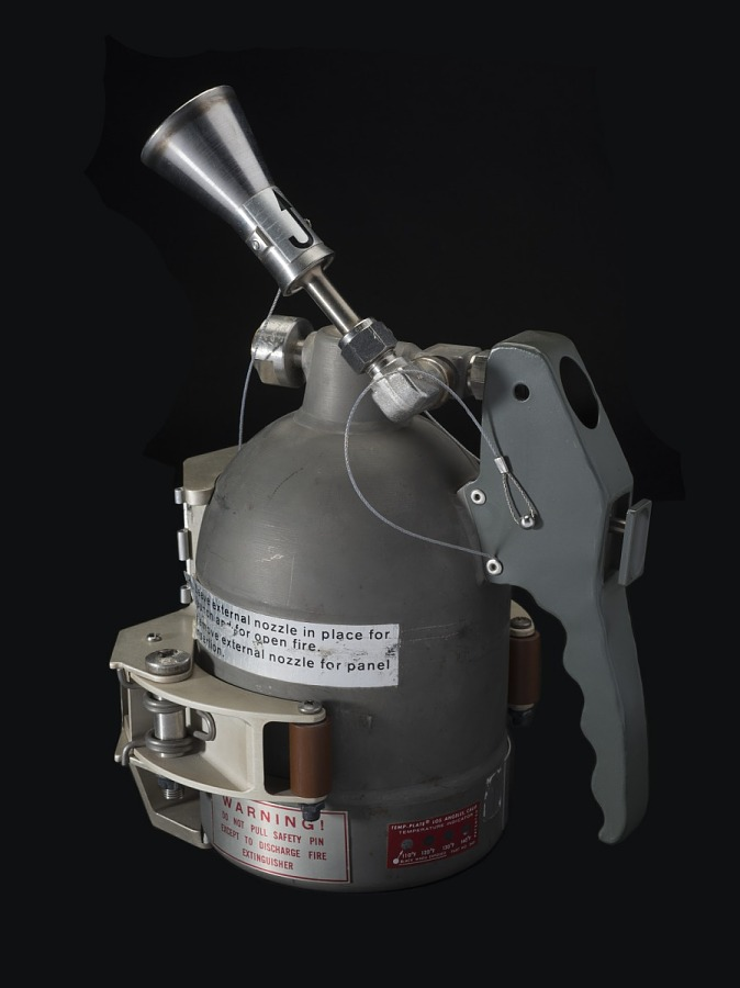Gray metal hand-held fire extinguisher with mounting bracket on Skylab Fire Extinguisher
