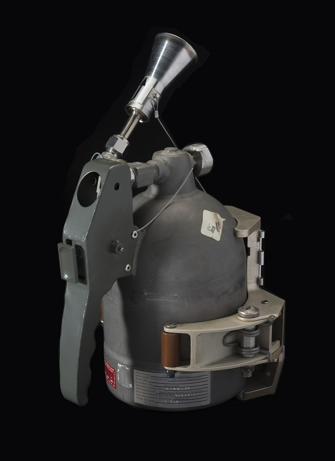 Back of gray metal hand-held fire extinguisher with mounting bracket on Skylab Fire                 Extinguisher