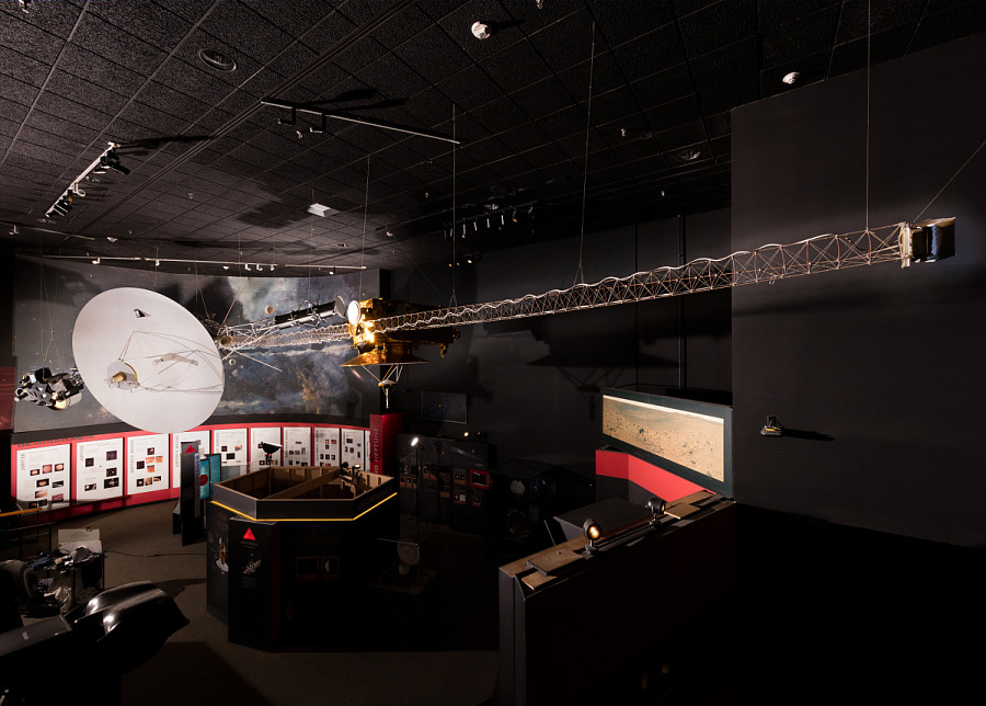 White circular disc with elongated metal truss of Voyager Spacecraft Full Scale Mock-up hanging                 in museum