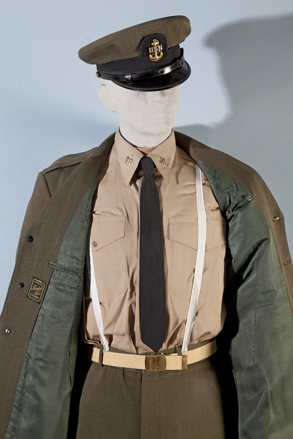 Olive-green button-down United States Navy Summer Service Shirt under opened coat on mannequin model with hat