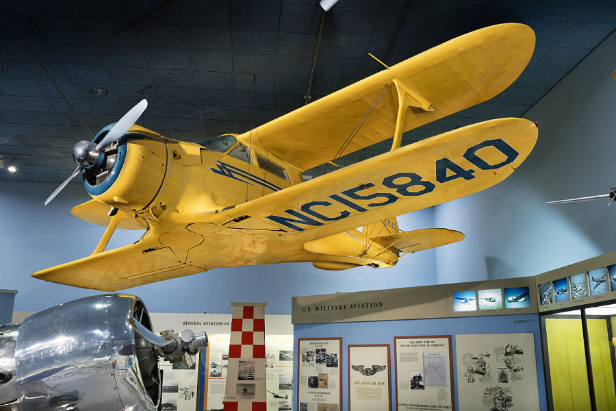 Overall view of yellow Beechcraft C17L Staggerwing on display at the museum