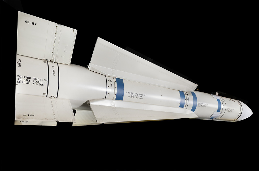 Cylindrical white missile with rectangular rear fins, long mid-body wings, blue stripes and                 black lettering