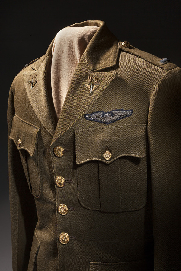Three quarter view of tan, four-button United States Army Air Corps Service Officer Coat with                 two pockets and insignia