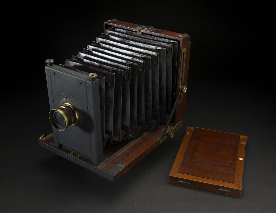 Front view of wooden box camera with black bellows and brass fittings, next to wooden                 photographic plate holder or dark slide