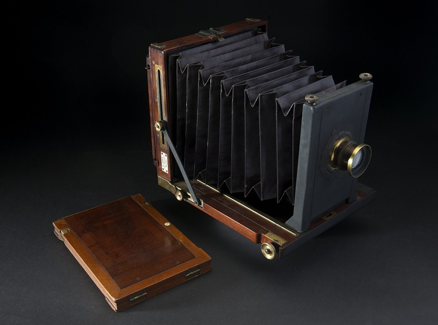Wooden box camera with black bellows, brass fittings, and maker's plate, next to wooden                 photographic plate holder or dark slide